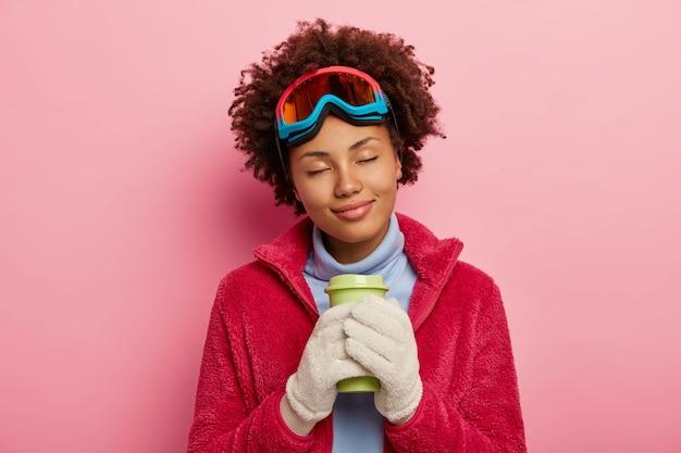 사랑스러운 여성 여행자의 사진은 겨울을 즐기고, 커피를 마시고, 눈을 감고, 부드럽게 미소를 짓고, 실내 포즈를 취합니다.
