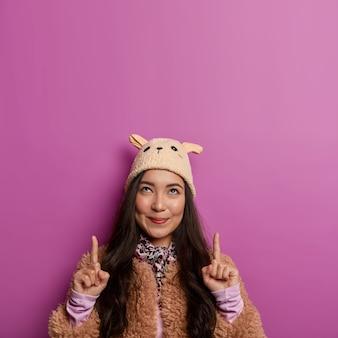 사랑스러운 소녀의 사진은 위의 두 검지 손가락을 가리키고, 복사 공간을 광고하고, 무언가를 위쪽으로 보여주고, 귀와 갈색 코트가 달린 모자를 쓰고 있습니다.