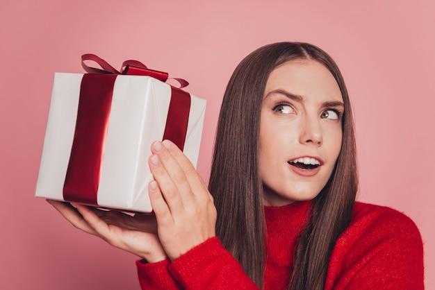 Фотография прекрасной девушки, получающей подарочную коробку, думает, что внутри, изолированное на розовом фоне