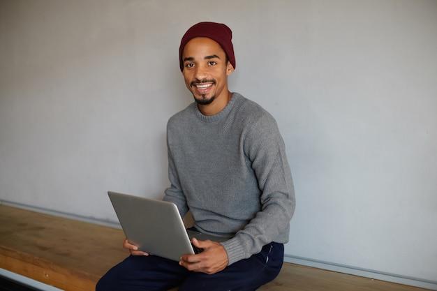 Фотография милого радостного темнокожего парня с бородой, сидящего на скамейке над конференц-залом и делающего презентацию для встречи, счастливо выглядящего и искренне улыбающегося