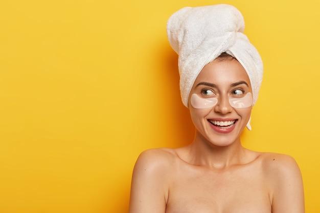 메이크업을 한 사랑스러운 자연 여성의 사진은 부드러운 미소로 옆으로 보이고 건성 피부 유형에 눈 밑 패치를 적용하고 수건을 착용합니다.