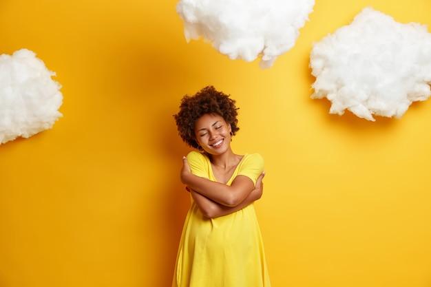 사랑스러운 임산부의 사진은 자신을 포용하고 긍정적으로 미소 짓고 출산에 대한 꿈을 꾸고 기쁨으로 눈을 감고 큰 배를 가지고 있으며 노란색, 구름 오버 헤드에 포즈를 취합니다. 미래의 어머니