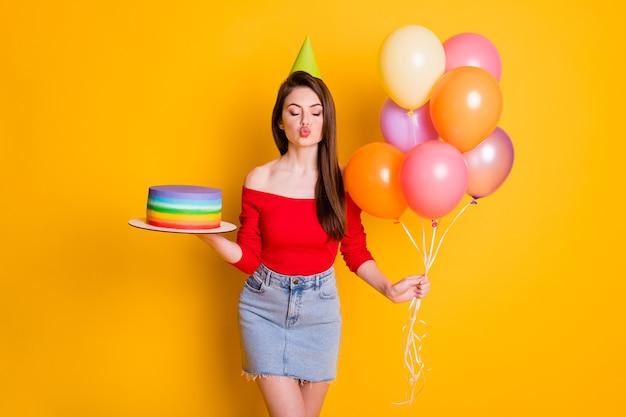 사랑스럽고 감사하는 어린 소녀의 사진은 눈을 감고 풍선 케이크를 입고 콘 셔츠를 입은 채 열린 어깨 데님 미니 스커트로 격리된 밝은 노란색 배경에서 공기 키스를 보냅니다.