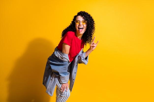 사랑스러운 젊은 여성의 혀를 내미는 쇼 뿔의 사진은 빨간색 티셔츠 줄무늬 청바지 재킷 선글라스로 분리된 노란색 배경을 입고 있습니다.