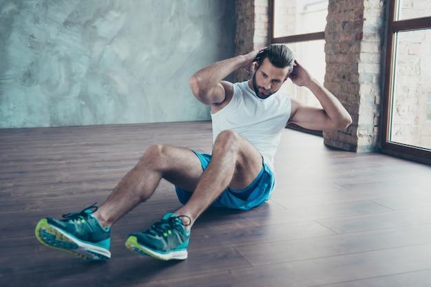Фотография спортсмена-мачо, который делает статические приседания, сидит на полу, решительный человек, спортивная одежда, майка, шорты, кроссовки, окна тренировочного дома, в помещении
