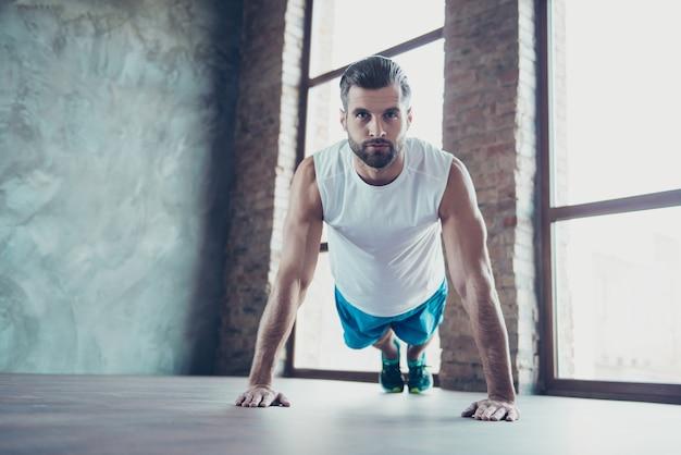 Фотография парня-мачо-спортсмена, показывающего клиенту, как правильно делать отжимания и планку, руки, опирающиеся на пол, спортивная майка, тренировочные окна дома в помещении