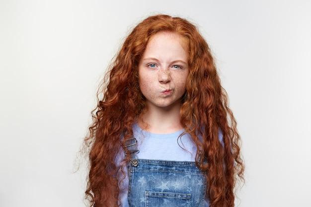 Фотография недовольной симпатичной веснушчатой маленькой девочки с рыжими волосами, родители запрещают смотреть мультики, сварливо смотрит в камеру, стоит на белом фоне.