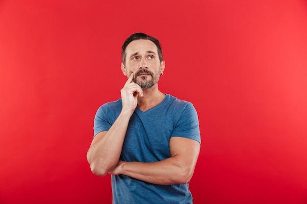 Фотография мужчины 30-х годов с задумчивым взглядом в повседневной футболке, глядя вверх и думать или вспоминать, изолированных на красном фоне