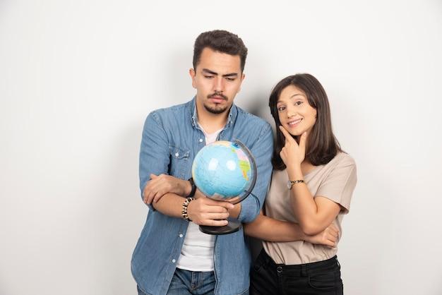 白の上に地球儀を保持している男性と女性の写真。