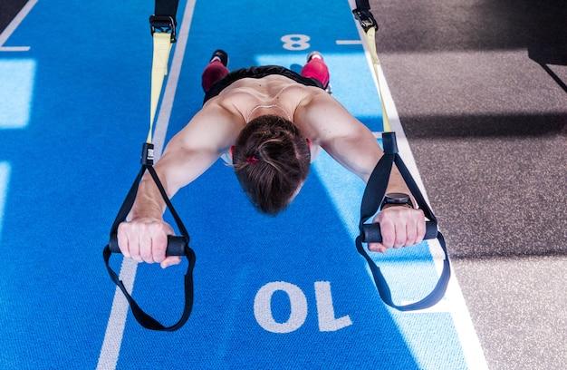 Фотография мужчины, делающего упражнения для сильного пресса в фитнес-ремнях trx в тренажерном зале