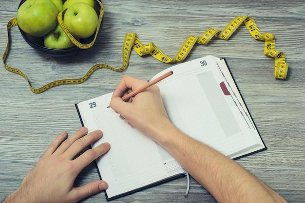 메모장에 쓰는 남자의 손 사진. 사과와 줄자로 가득 찬 그릇의 위쪽 전망은 회색 나무 테이블을 측정합니다.