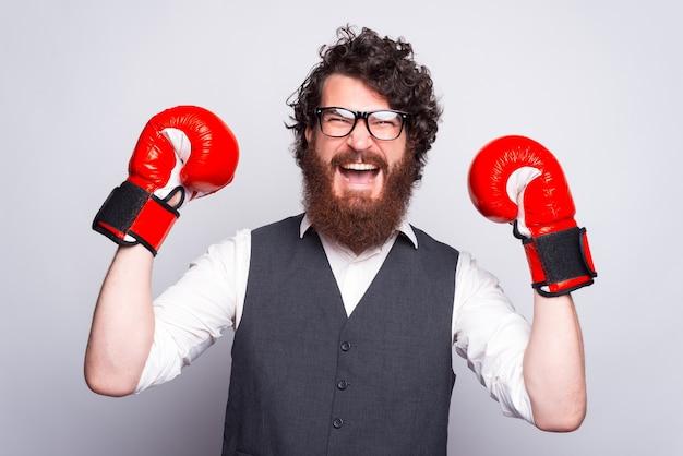 Фотография мужчины в костюме и боксерских перчатках, празднующих и кричащих
