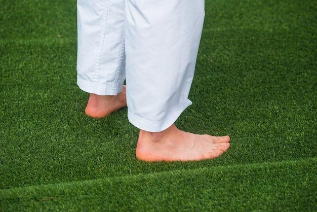 Фотография человека с босой ногой, сидящего на свежей зеленой траве