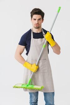 Фотография мужского молодого человека в желтых резиновых перчатках для защиты рук, держащего швабру во время уборки дома, изолированного на белом