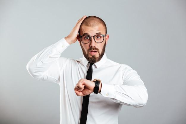 腕時計を探していると灰色の壁に分離された頭をつかんでビジネス衣装で成熟した男30代の写真