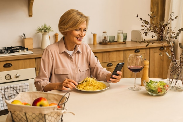 Фото зрелой положительной старшей женщины, сидящей на кухне в помещении дома с помощью мобильного телефона.