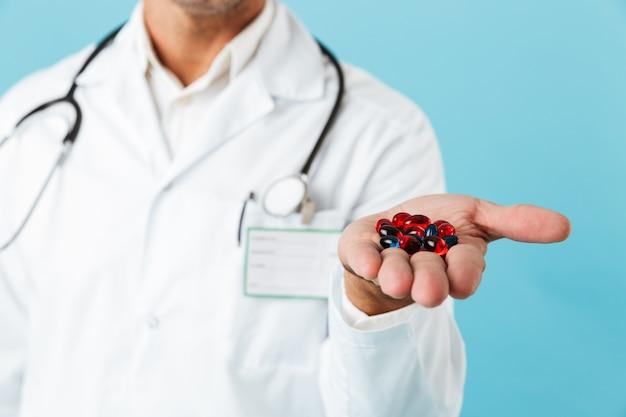 青い壁の上に孤立して立って、手のひらに丸薬を保持している白いコートを着ている医師の写真