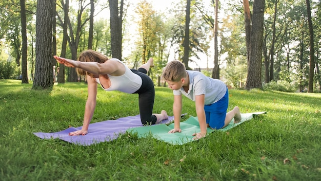 요가를 하는 10대 소년을 가르치는 중년 여성 요가 교사 또는 전문가의 사진. 소년 명상과 공원에서 잔디에 스트레칭 여자