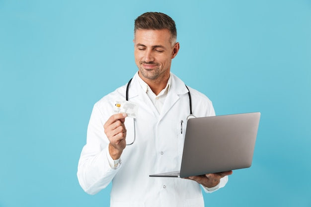 ラップトップとクレジットカードを保持し、青い壁の上に孤立して立っている白い医療コートと聴診器を身に着けている中年男性の写真