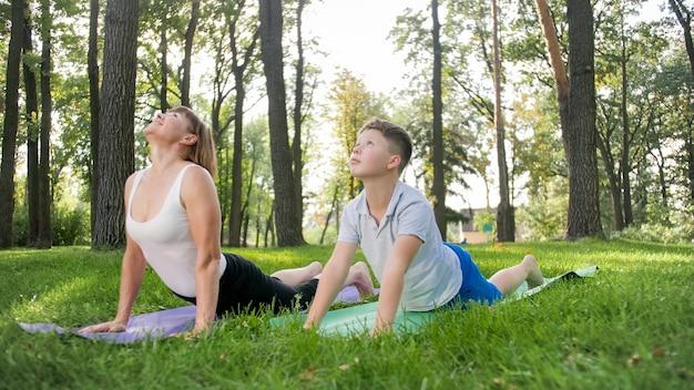 공원에서 요가와 호흡 운동을 하는 10대 소년 아이와 함께 있는 중년 어머니의 사진. 스포츠를 하면서 자신의 정신적, 육체적 건강을 돌보는 가족