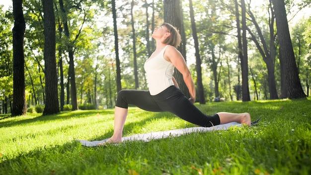 中年の笑顔の女性がヨガを練習し、公園で瞑想している写真。森のマットの上でストレッチとフィットネスをしている女性