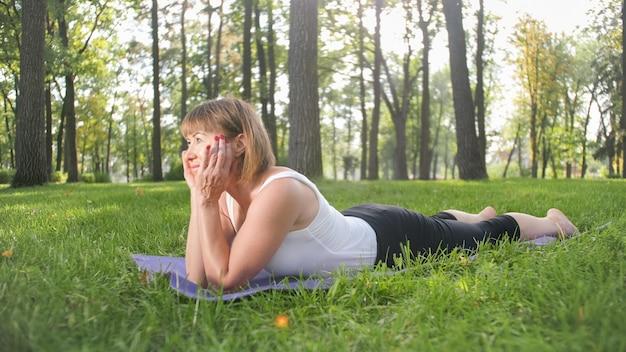 Фотография улыбающейся женщины средних лет, практикующей йогу и медитирующей в парке. женщина растягивается и занимается фитнесом на коврике в лесу