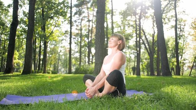 ヨガのアーサナを練習している中年の笑顔の女性の写真。自然の中で瞑想している人。心と体のバランスと調和