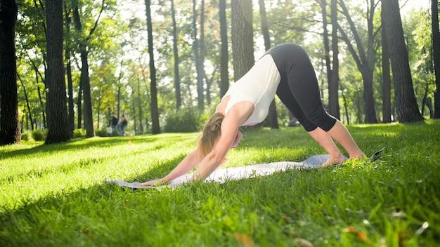 公園で屋外でヨガを練習しているスポーツ服を着た中年女性の写真。森でストレッチと瞑想中年女性