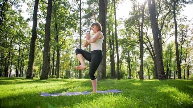 공원의 신선한 녹색 잔디에서 요가나 피트니스를 연습하는 중년 여성의 사진. 여성의 신체적, 정신적 건강. 명상과 조화 pf 몸과 영혼의 사람