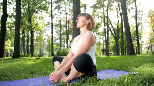 公園で新鮮な緑の芝生でヨガやフィットネスを練習している中年女性の写真。女性の心身の健康。瞑想と調和のとれた人体と魂