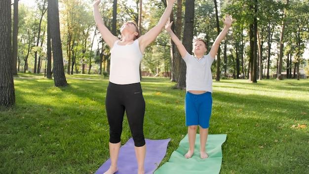 Фото женщины средних лет, обучающей своего ученика в классе йоги в парке. woamn с подростком, практикующим фитнес, медитацию и йогу на траве в лесу