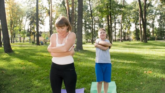 Фотография женщины средних лет с 12-летним мальчиком-подростком, практикующим йогу и медитирующим в парке. семья отдыхает и занимается фитнесом на природе