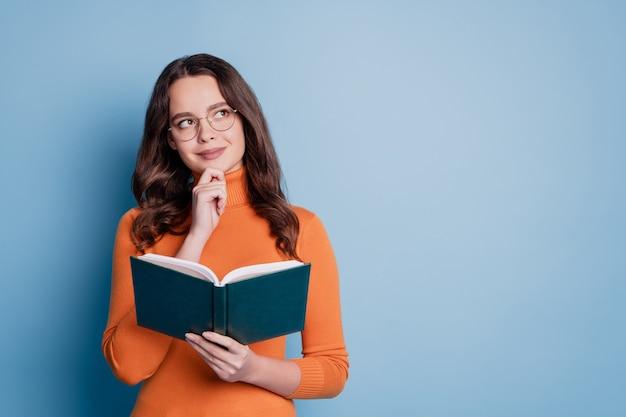 Фото мыслящей умной творческой женщины, читающей книгу, подбородок пальца, взгляд пустое пространство, позирующее на синем фоне