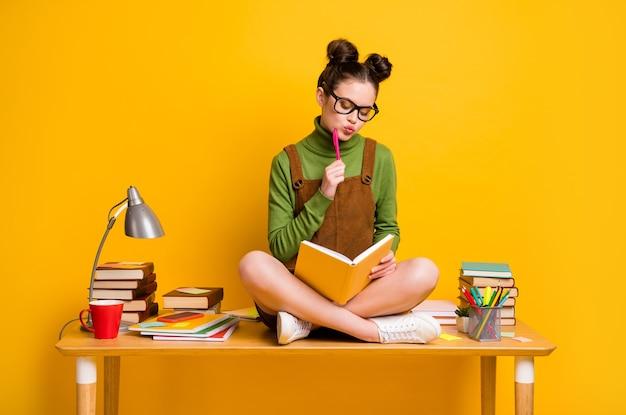 생각하는 소녀의 사진은 노란색 배경에 대해 생각하는 카피북 쓰기 테이블에 앉아 있습니다.