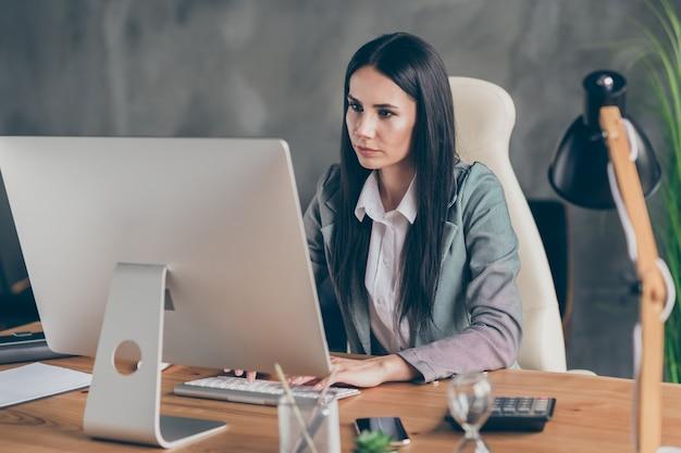 気にされた物思いにふける女の子エージェントマーケターの上司の写真座るテーブルワークリモートコンピューター閲覧スタートアップ危機成長情報職場のワークステーションでフォーマルなジャケットブレザーを着用