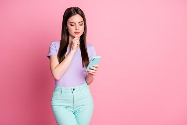 Фото настроенной smm-девушки, использующей смартфон, думают, мысли, решают, что делать в социальной сети, размещать одежду, бирюзовые штаны, фиолетовую одежду, изолированную на розовом цветном фоне