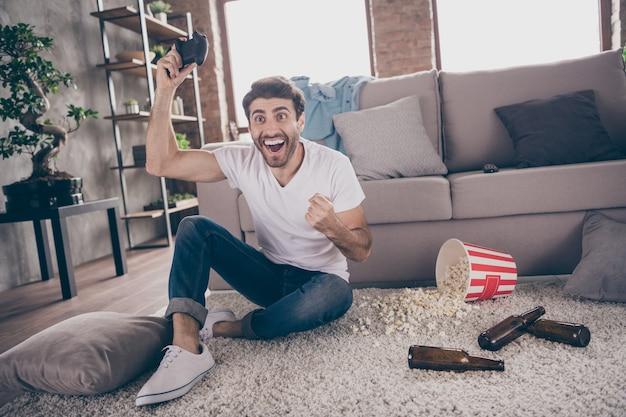 Фотография арабского парня смешанной расы, сидящего на ковре возле дивана, держит джойстик, играет в видеоигру, взволнованная победа, поднимает кулаки, пустые пивные бутылки, попкорн на полу, беспорядок, квартира