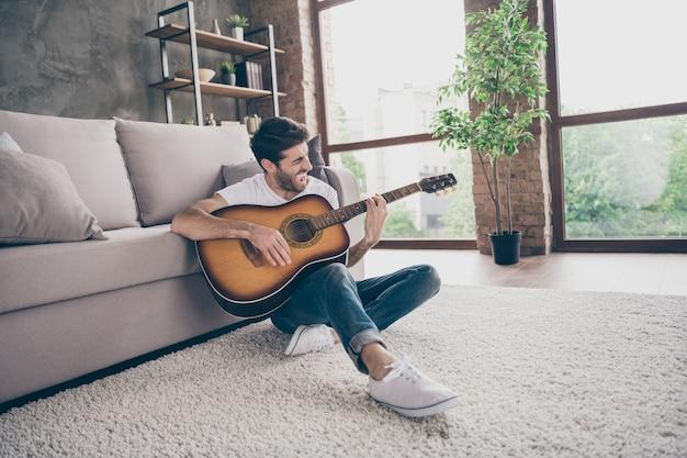 혼혈 남자 앉아 바닥 기울고 소파 홀드 어쿠스틱 기악 기타 연주 신작 노래 소리 서명 창의적인 재능있는 사람 평면 로프트 거실 실내 사진