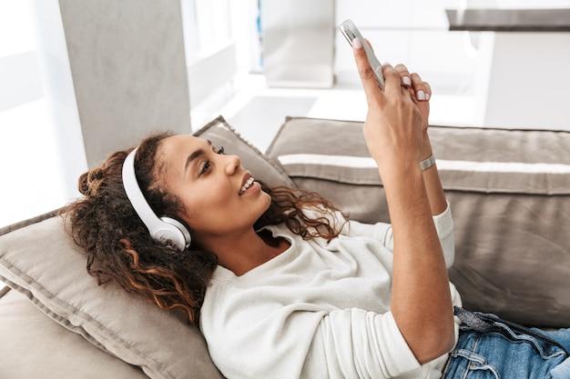 明るいアパートのソファに横たわっている間、携帯電話を保持しているヘッドフォンを身に着けている現代のアフリカ系アメリカ人女性の写真