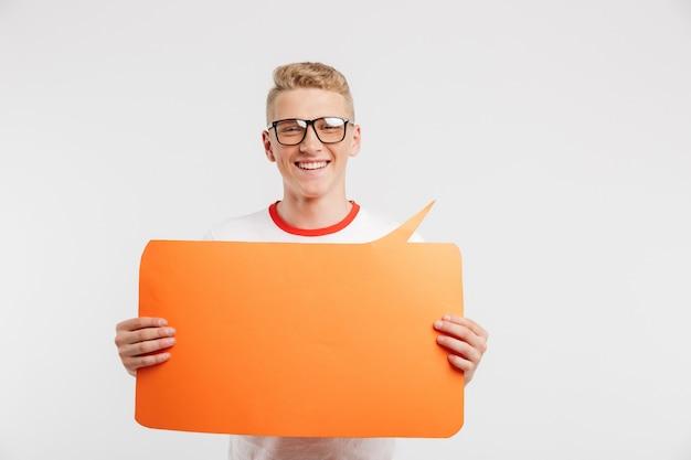 カジュアルな服と白で隔離の手で空白のオレンジ色のバナーを保持している眼鏡を身に着けている現代の若者の写真