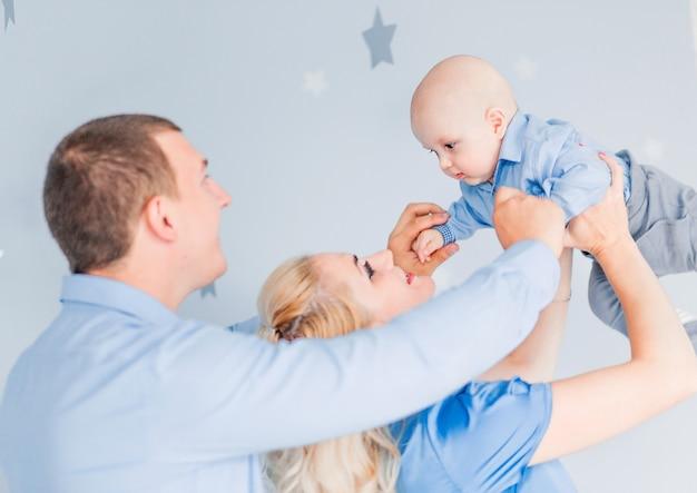 ママとパパの写真が赤ちゃんを投げて遊んでいます