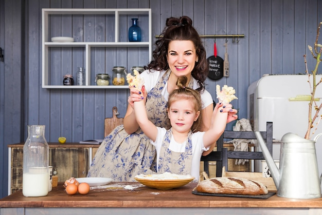 Фото мамы и дочки вместе готовят на кухне