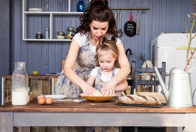ママと娘の写真がキッチンで一緒に調理します。