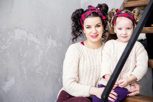 階段に一緒に座っている母と娘の写真