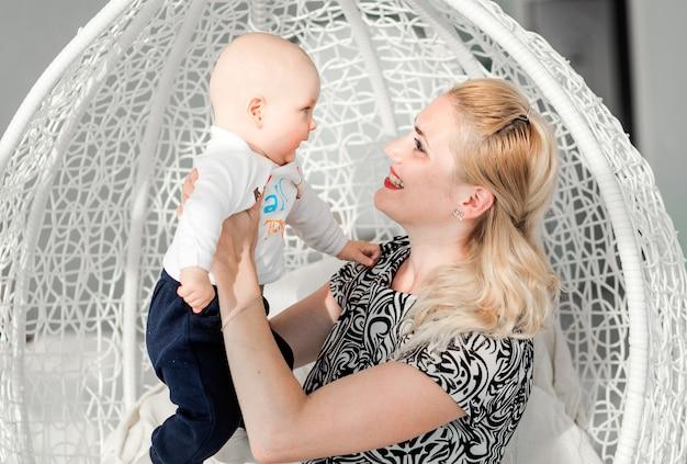 Фотография матери и сына сидят в модном круглом кресле