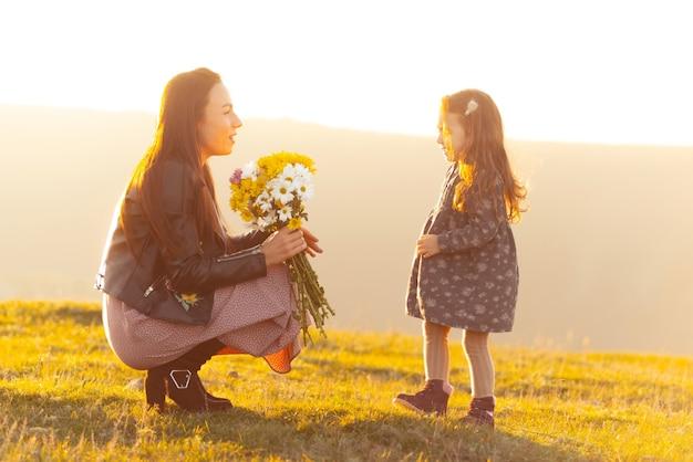 日没時に彼女の小さな娘に花を与える母親の写真