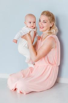 ピンクのドレスを着た母親の写真は彼女の腕と笑顔で小さな息子を保持しています