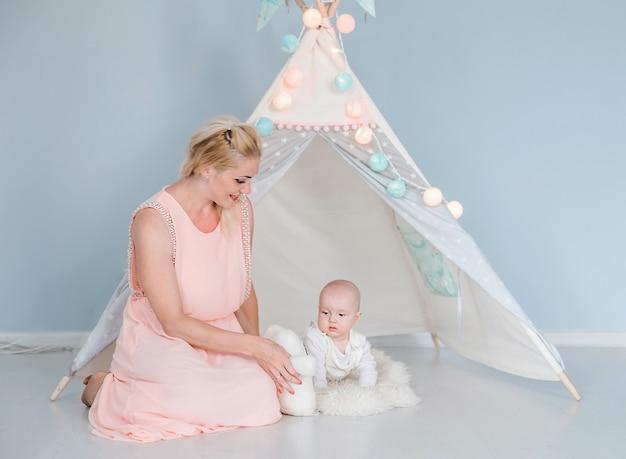 子供のテントの近くの部屋で息子と遊ぶ母親の写真