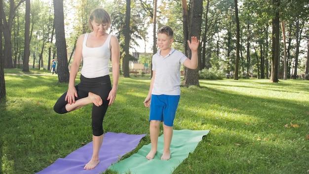 公園の芝生でヨガのアーサナを練習している10代の少年の息子と母親の写真。森でフィットネスやスポーツをしている家族 Premium写真
