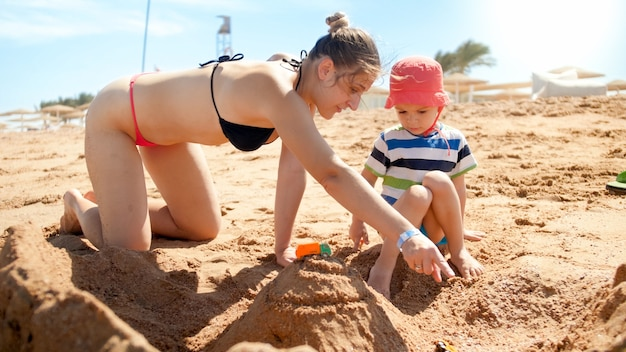 海のビーチで砂の城を作る幼い息子を持つ母の写真。海でくつろぐ人々。夏休みに家族で休んで楽しんでいます。